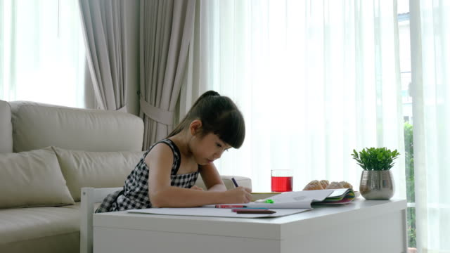 Asian Cute little child kindergarten girl is drawing and painting with colorful felt-tip pens in living room at home. Asian Cute little child kindergarten girl is drawing and painting with colorful felt-tip pens in living room at home. playroom stock videos & royalty-free footage