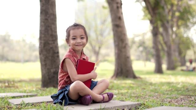 vidéos et rushes de asiatique mignonne petite fille dessin dans le parc public. concept d'éducation. - fournitures scolaires