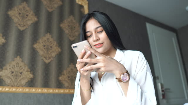 Asian cute young girl using mobile smartphone in her bedroom video