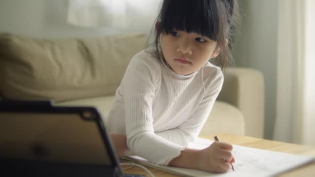 asiatiska dotter sköter online-klass hemifrån. - digital reading child bildbanksvideor och videomaterial från bakom kulisserna