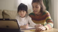 istock Asian daughter attending to online class from home with mother. 1216651025