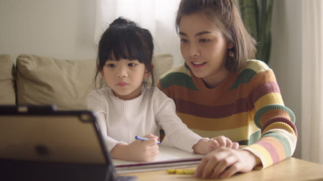 asian daughter attending to online class from home with mother. - электронное обучение стоковые видео и кадры b-roll