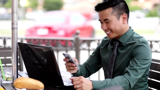 Asian descent business man working at outdoor cafe. video