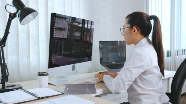 Asian Developing Concentrated programmer reading computer codes Development Website design and coding technologies.