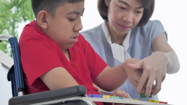 anne veya bakıcı ile tekerlekli sandalyede asyalı engelli çocuk evde birlikte faaliyetleri uygulama becerileri bulmaca oyunu yapıyor. engelli - giving tuesday stok videoları ve detay görüntü çekimi