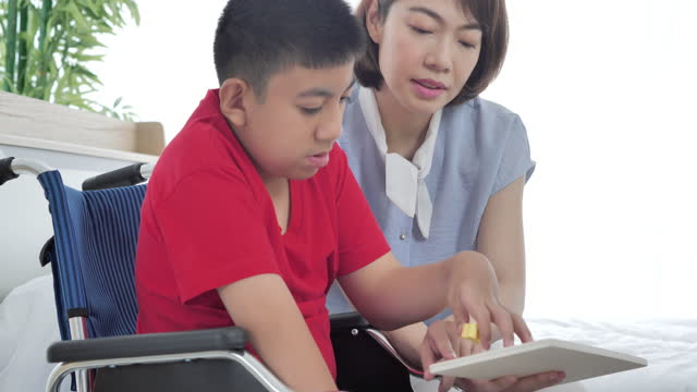 Asian disabled boy in wheelchair with mother or caregiver doing activities practice skills puzzle game together at home.The Disability Collection 2019 Asian disabled boy in wheelchair with mother or caregiver doing activities practice skills puzzle game together at home. Disability, Education, Supportive, Care, Family, Volunteer, Caretaking, Children education, Homeschooling concept. giving tuesday stock videos & royalty-free footage