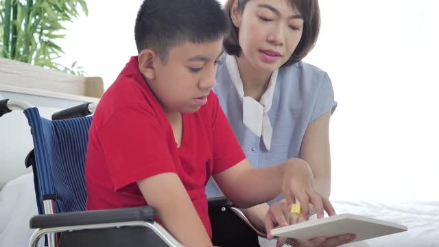 어머니 또는 간병인과 함께 휠체어를 탄 아시아 장애인 소년은 집에서 함께 운동 연습 기술 퍼즐 게임을하고 있습니다. 장애인 컬렉션 2019 - giving tuesday 스톡 비디오 및 b-롤 화면