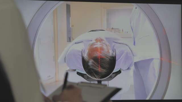 vidéos et rushes de femme de docteur asiatique avec le personnel de soins de santé observent dans une salle de balayage dans un nouvel hôpital moderne de traitement par le patient aîné d'homme est scanné par mri, procédure de tomodensitomètre de ct. examen de résona - tomographie