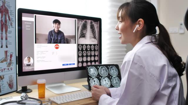 vídeos de stock e filmes b-roll de asian doctor having telemedicine consultation to a patient - exame médico procedimento médico
