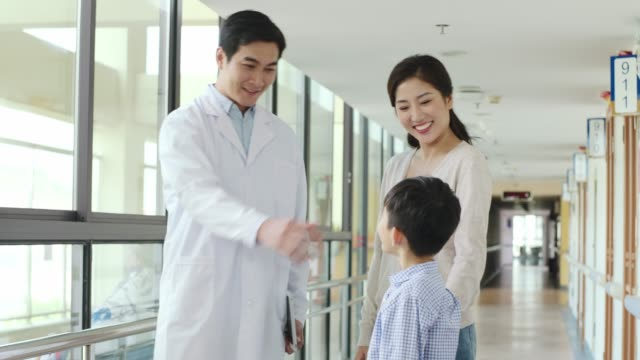 asian doctor talking to mother and son in hospital