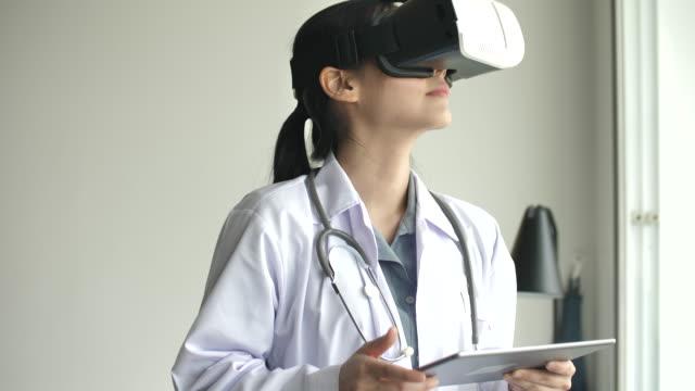 azjatycki lekarz za pomocą okularów vr, zestaw słuchawkowy wirtualnej rzeczywistości dla służby zdrowia - rzeczywistość witrualna filmów i materiałów b-roll