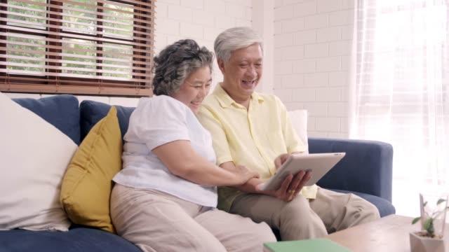 stockvideo's en b-roll-footage met aziatische ouderen echtpaar met behulp van tablet tv kijken in de woonkamer thuis, echtpaar genieten van liefde moment liggend op de sofa wanneer ontspannen thuis. genieten van time lifestyle senior family at home concept. - oost aziatische cultuur