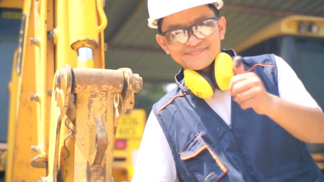 Asian engineer Check examines a scheme of a excavator, slow motion.