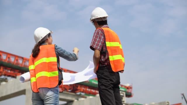 vidéos et rushes de ingénieur asiatique travailleurs discute un projet - route surélevée