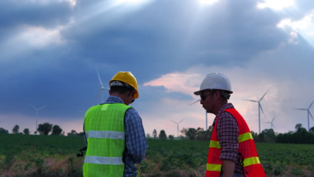 Asian engineers male, two people holding hands to show success in the work of wind turbines in wind farm field for production of electric power Asian engineers male, two people holding hands to show success in the work of wind turbines in wind farm field for production of electric power generation x stock videos & royalty-free footage
