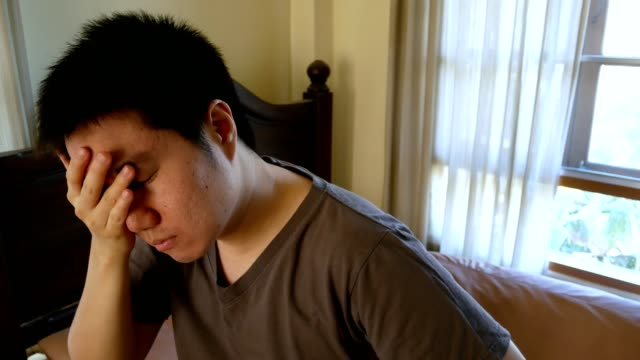 asian exhausted man waking up in the morning and rubbing his face video