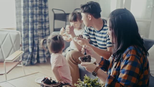 vídeos de stock e filmes b-roll de asian family celebrating birthday and eating cake in the living room (slow motion) - bolo sobremesa
