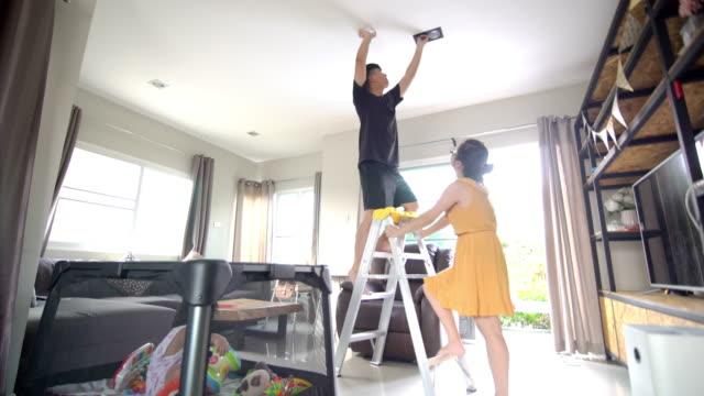 asiatische familie wechselt glühbirne zusammen im wohnzimmer - led leuchtmittel stock-videos und b-roll-filmmaterial