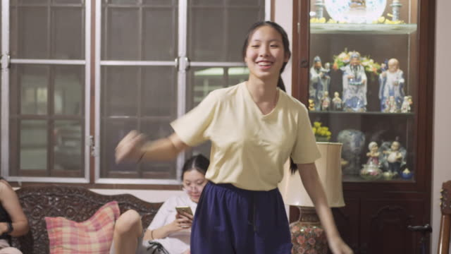 pan asian family dancing in living room - porcellana video stock e b–roll
