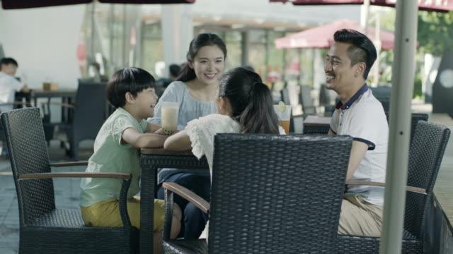 アジア家族飲み・屋外スローモーションで幸せな家族の時間を楽しむ席で話して ビデオ