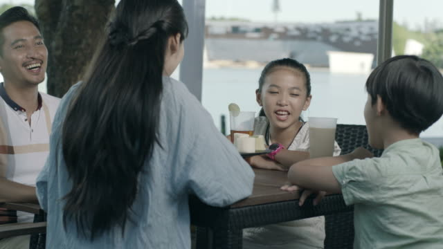 asian family drinking & talking at outdoor seating enjoying happy family time in slow motion video