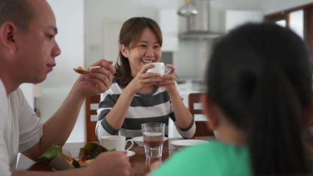 asiatisk familj äta frukost och njuta av tiden med familjen - kinesiskt ursprung bildbanksvideor och videomaterial från bakom kulisserna