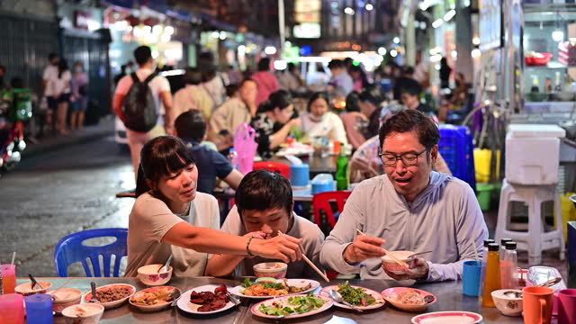 4K Asian family eating food on street food restaurant at Bangkok Chinatown with traffic