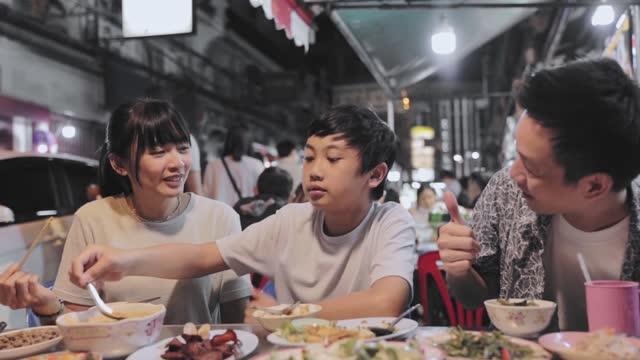 Asian family eating in Street food Night market for tourist on chinatown at yaowarat road in Bangkok