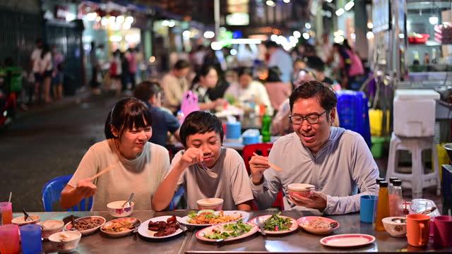 4K Asian family enjoy eating food on street food restaurant with crowd of people at Yaowarat road, Bangkok