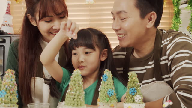 Asian Family Father Mother and Daughter decrorate cupcake