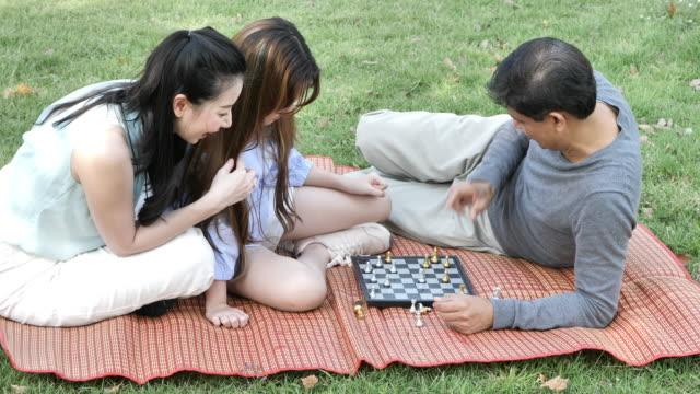 asiatischen familie, vater, mutter und tochter spielen checker spiel zusammen im park an einem sonnigen tag. entspannen sie in den wald-frühling-sommer. slow-motion - bauholz brett stock-videos und b-roll-filmmaterial