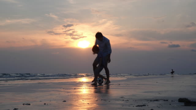 vídeos de stock e filmes b-roll de asian family happy playing football on the beach summer together in holiday. father and son kick football together. concept of family, travel, summer and sport. 4k resolution. - bebé praia