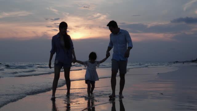 アジアの家族はリラックスして、休日に一緒にビーチの夏に休息を楽しみます。家族、旅行、夏と休暇の概念。4k解像度。 - 息子点の映像素材/bロール