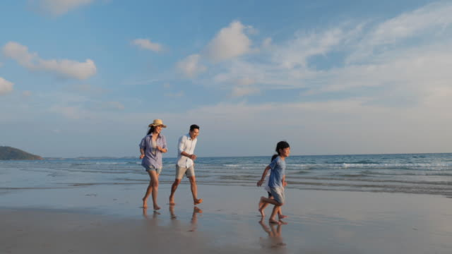 Asian family happy walking relax and resting on the beach summer together in holiday. Concept of family, travel, summer and vacation. 4k resolution.