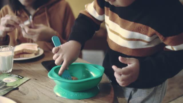 アジア系の家族が朝食を持っています。 - テーブル点の映像素材/bロール