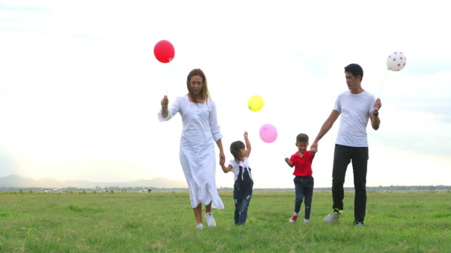 Asian family holding balloon and walking on the Meadow at sunset with happy emotion. Family Holiday and Travel concept.