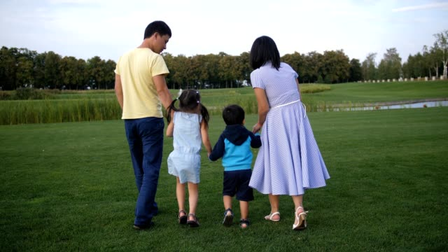 Asian family holding hands and walking outdoors