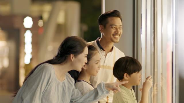 stockvideo's en b-roll-footage met aziatische familie van 4 permanent & op zoek naar etalage in slow motion - oost azië
