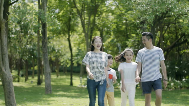 asian family of 4 walking & laughing in park in sunny summer in slow motion video