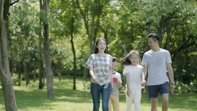stockvideo's en b-roll-footage met aziatische familie van 4 lopen & lachen in park in zonnige zomer in slow motion - oost azië
