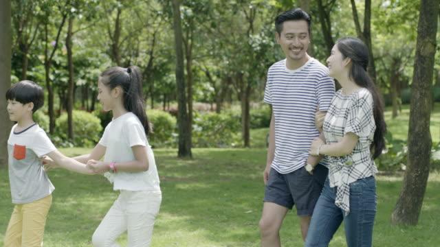 4 ウォーキング ・ スローモーションで日当たりの良い夏の公園で笑いのアジア家族 - 家族 日本人点の映像素材/bロール