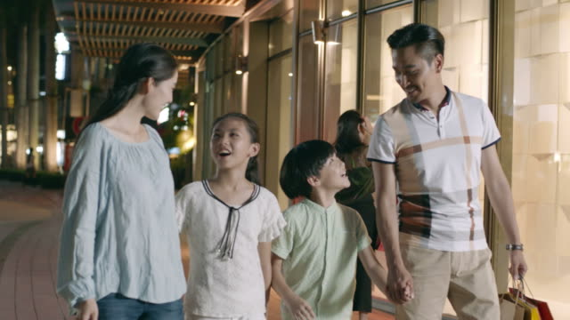 asian family of 4 walking & shopping outside a shopping mall at night in slow motion video