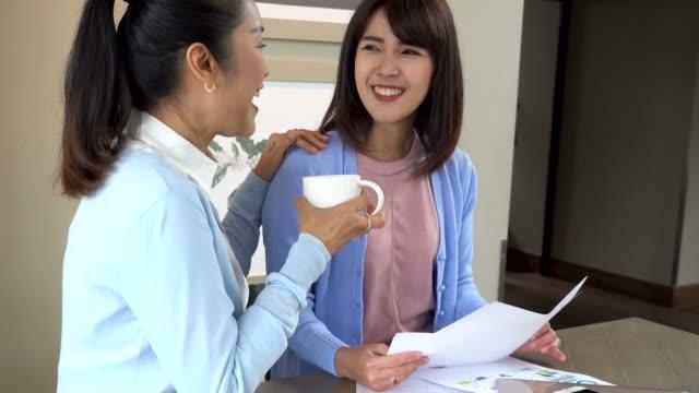 中間のアジア家族歳女性や若い 10 代の娘の話、喫茶店で笑顔 ビデオ