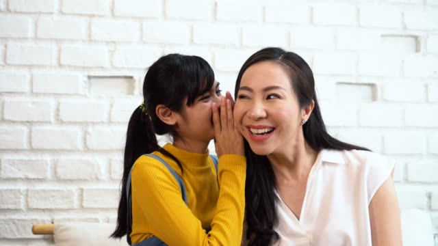 asian family of teenage girl gossiping at mature woman's ears at home - ear talking video stock e b–roll
