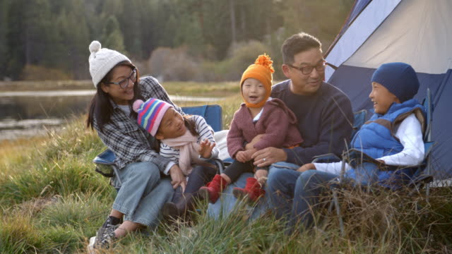 Asian family on a camping trip relaxing outside their tent video