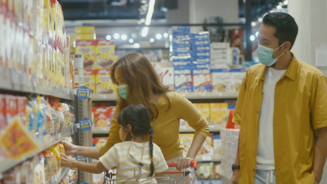Asian family out shopping at supermarket. Asian family out shopping for groceries together at their local supermarket. snack aisle stock videos & royalty-free footage