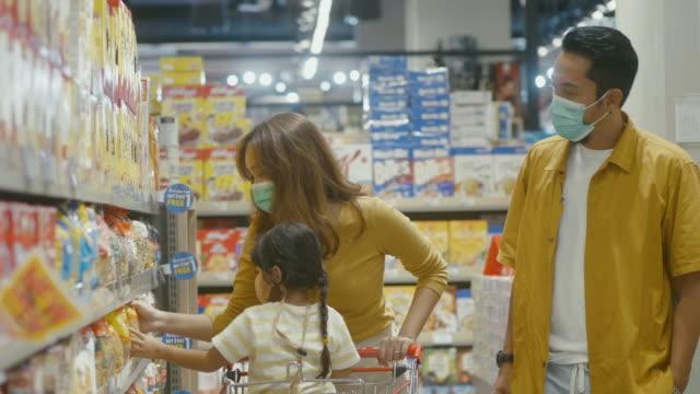 vídeos y material grabado en eventos de stock de familia asiática de compras en el supermercado. - snack aisle