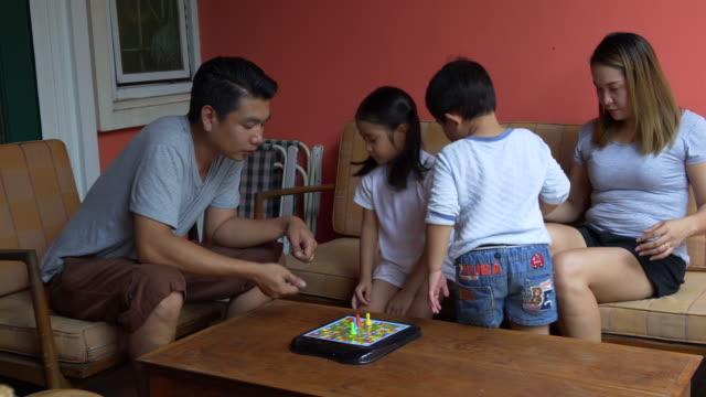 vídeos de stock, filmes e b-roll de família asiática jogando jogo de dados em casa - salas de aula