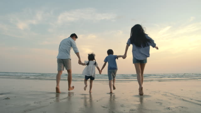 SLOW MOTION - Asian family running on the beach at sunset with happy emotion. Family, Holiday and Travel concept. Back Rear View. Family, Child, Running, Sunset, Beach holiday stock videos & royalty-free footage