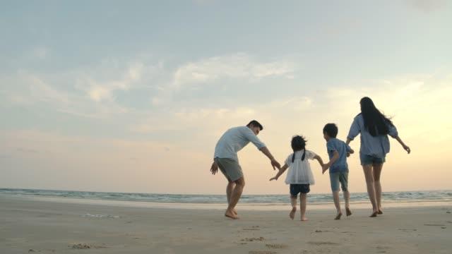 スローモーション-幸せな感情と日没時にビーチで実行されているアジアの家族。家族、休日、旅行のコンセプト。背面の背面図。 - 母娘 笑顔 日本人点の映像素材/bロール